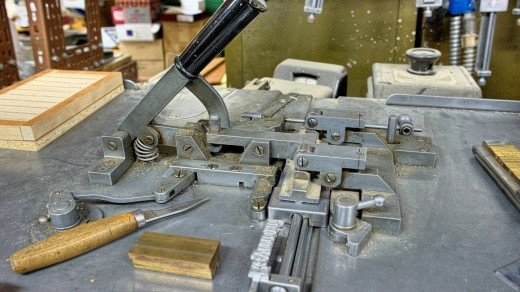 2015-01-18_0RA9471_v1_LTM_PC | The composing stick was then locked into the Ludlow machine as shown here. A lever on the front of the machine was then activated which injected typographic metal into the matrices to create a slug.