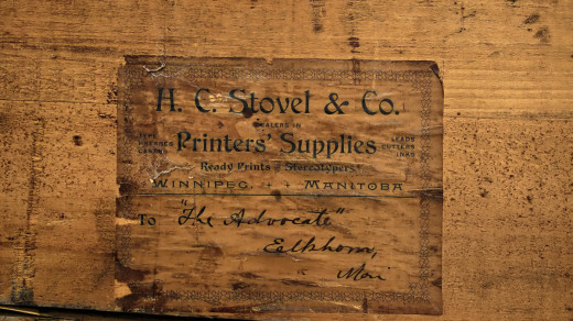 "2015-06-05_0RA9817_v1 EDIT-PC-TM2 1200 | Antique type case dating to pre 1906. Label reads ""H.C. Stovel & Co. Printers Supplies. Ready Prints, Stereotypers. Winnipeg, Manitoba. To: ""The Advocate"", Elkhorn, Manitoba.   Note: Wikipedia notes that the Advocate was established in 1892 and ceased operation in 1910. (https://en.wikipedia.org/wiki/Elkhorn,_Manitoba)."
